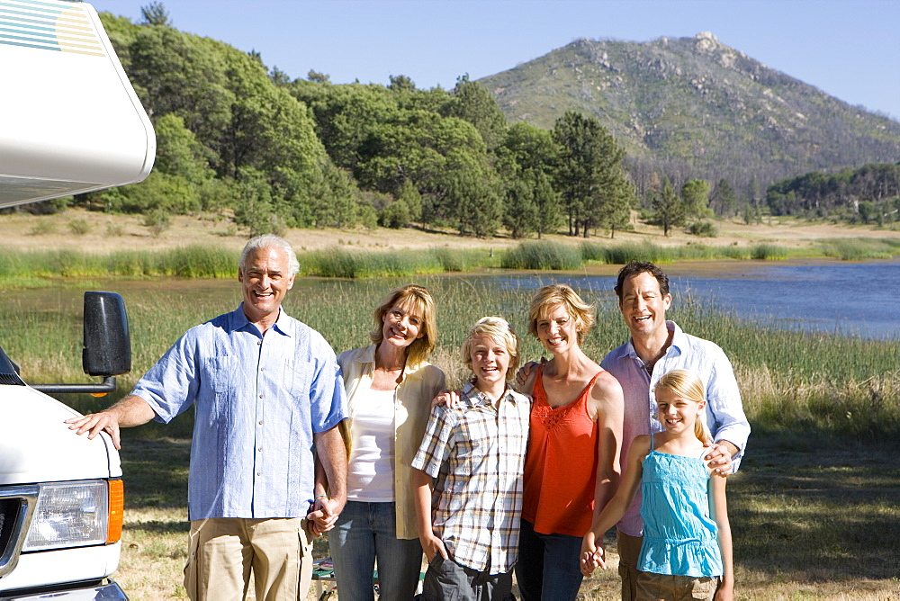 Family of three generations arm in arm by motor home by lake, smiling, portrait