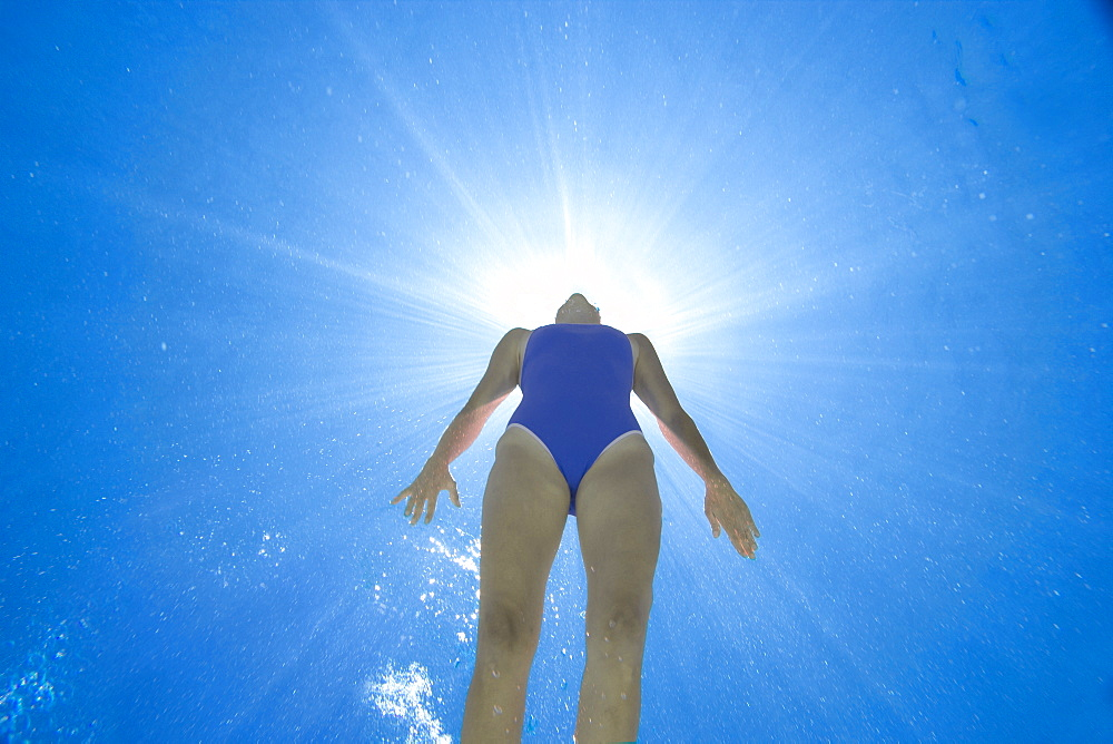Woman in swimming pool, underwater view (lens flare) - 786-4047