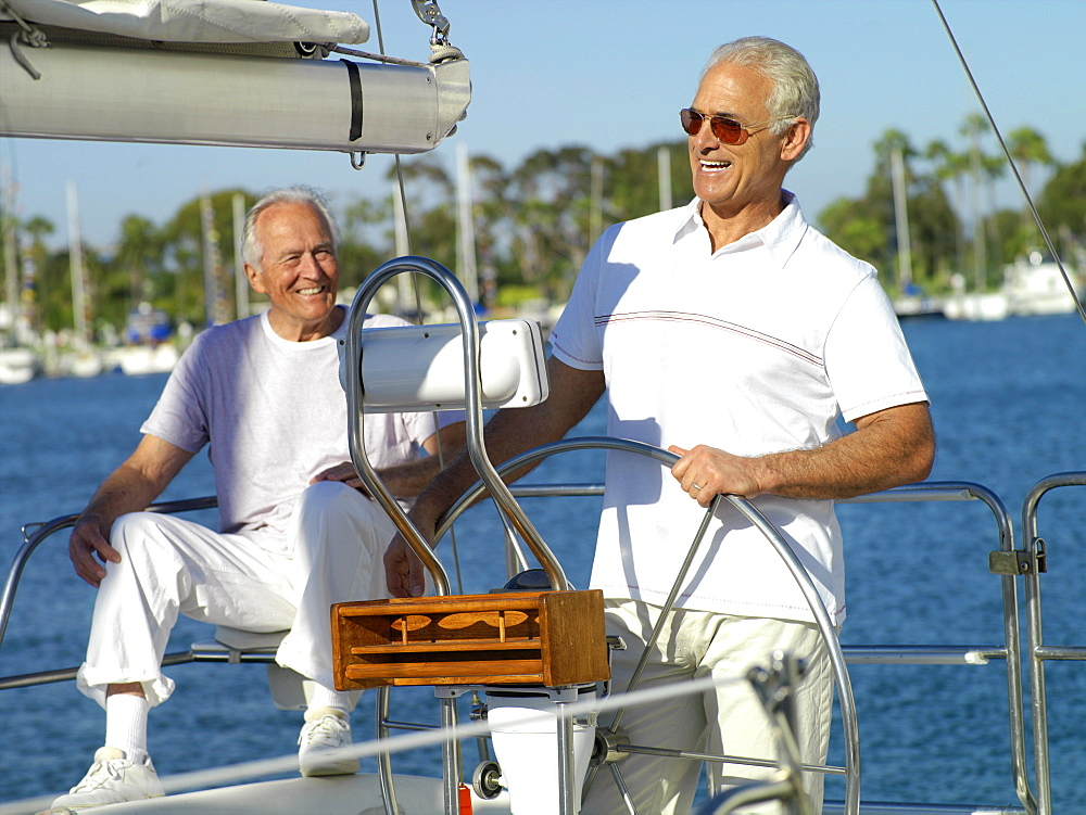 Mature man at wheel of boat by friend, smiling
