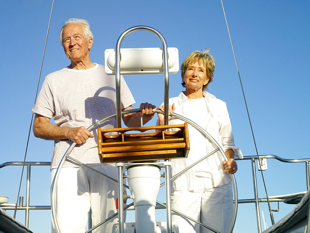 Senior couple at wheel of boat, smiling, low angle view