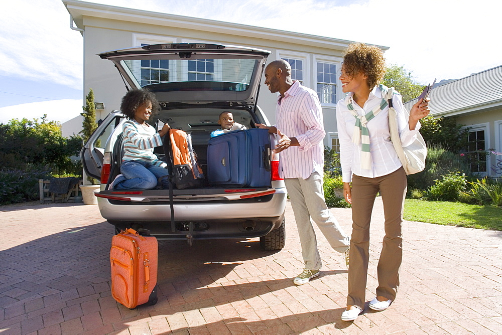 Parents smiling at children (8-10) siiting in boot of car with suitcases