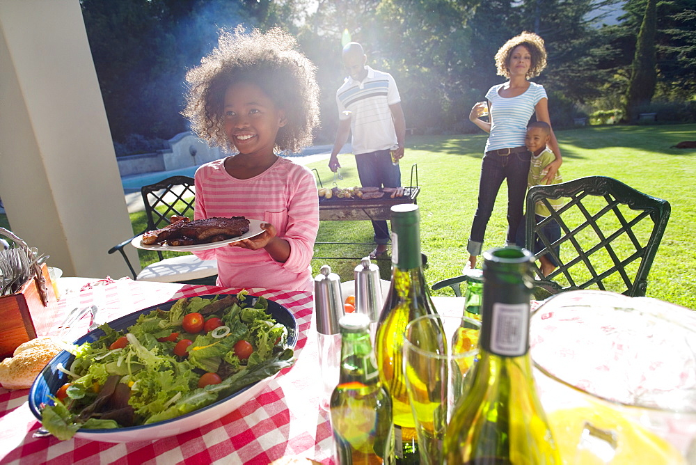 Family having barbeque outdoors, smiling