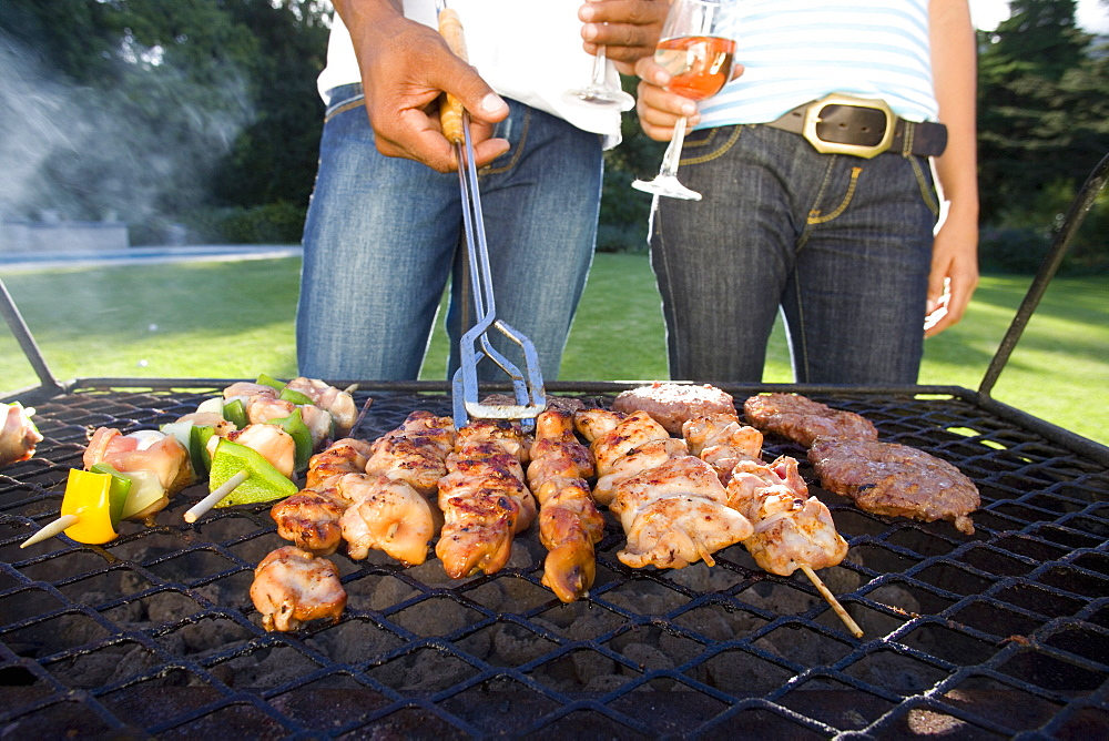 Couple having barbeque outdoors, standing by grill, mid section