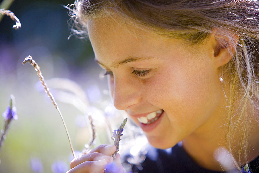 Girl (8-10) in field, smiling, close-up