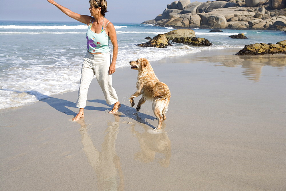 Mature woman with dog on beach, arm outstretched