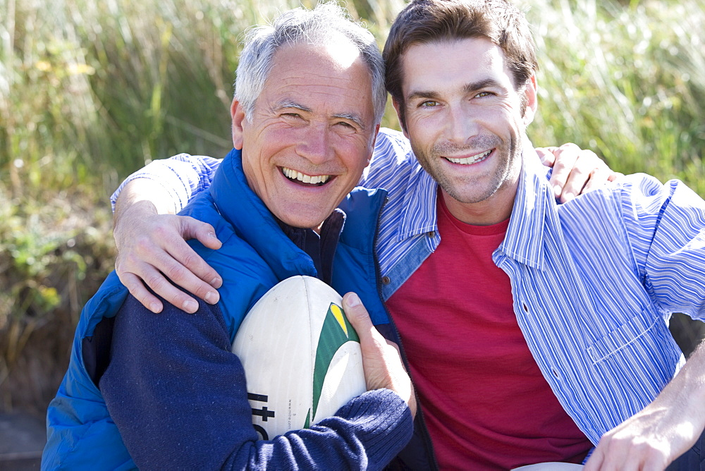 Portrait of two men holding rugby ball on beach