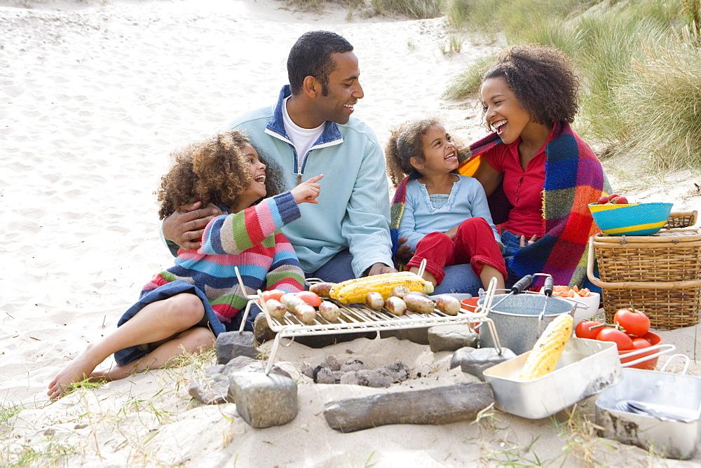 Family preparing barbecue on beach