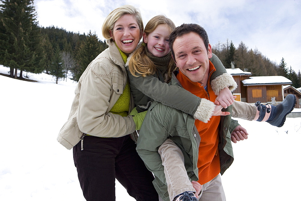 Portrait of young family with daughter in snow