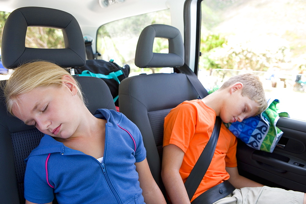 Brother and sister (8-12) asleep in back of car, close-up