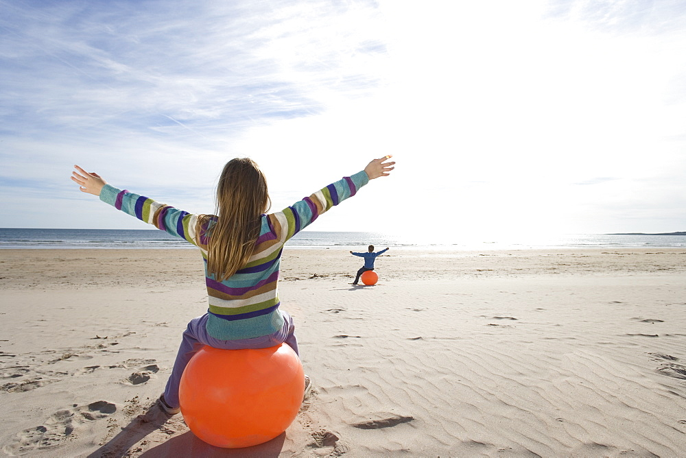 Girl and boy (8-12) on inflatable hoppers on beach, arms outstretched, rear view