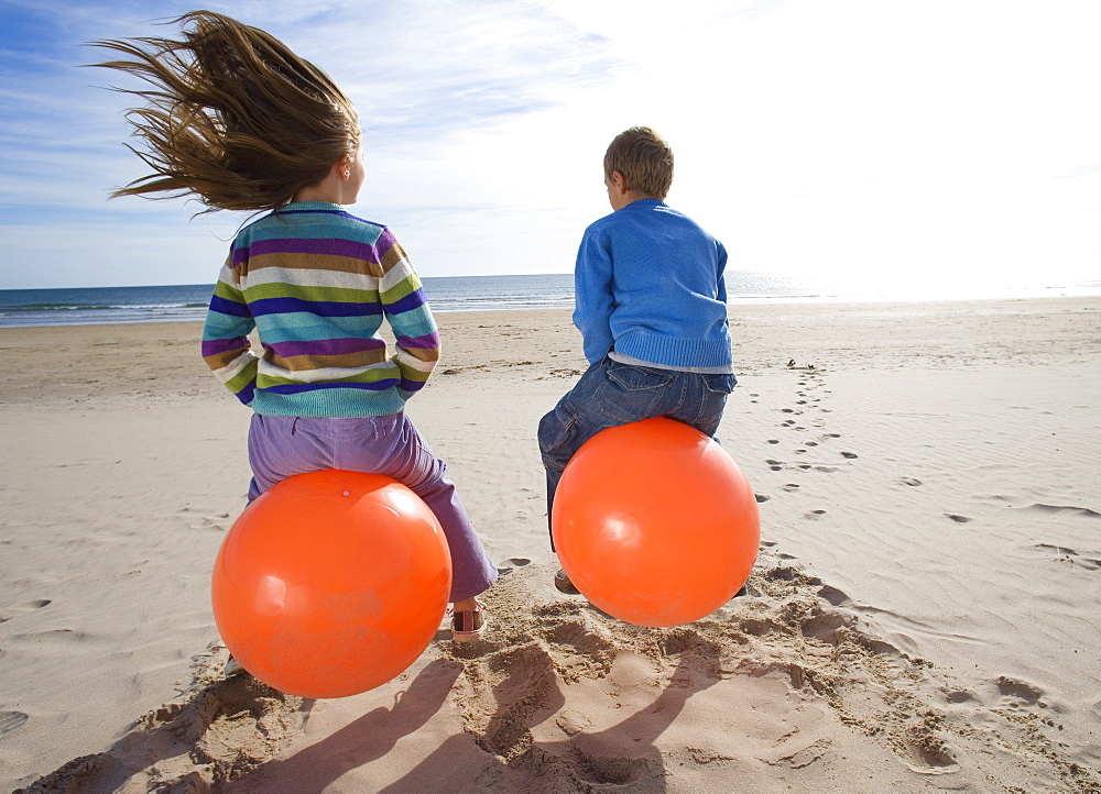 Girl and boy (8-12) playing on inflatable hoppers on beach, rear view