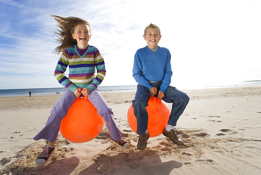 Girl and boy (8-12) playing on inflatable hoppers on beach, smiling, portrait
