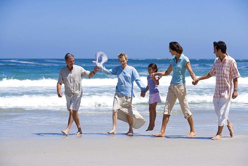 Family of three generations walking on beach, holding hands