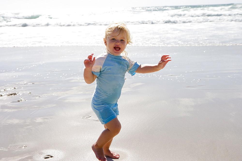 Girl (2-4) on beach, smiling