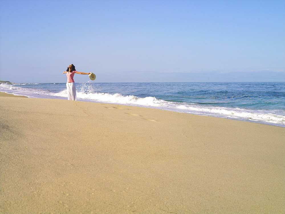 Woman on beach with arms outstretched, looking up