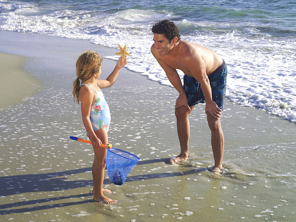 Girl (3-5) showing father starfish on beach