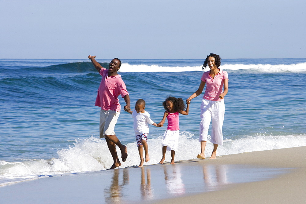 Family of four walking on beach - 786-5153