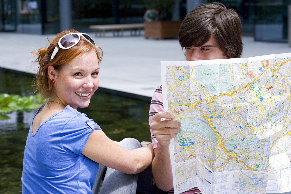 Young couple with map, portrait of woman smiling - 786-5173