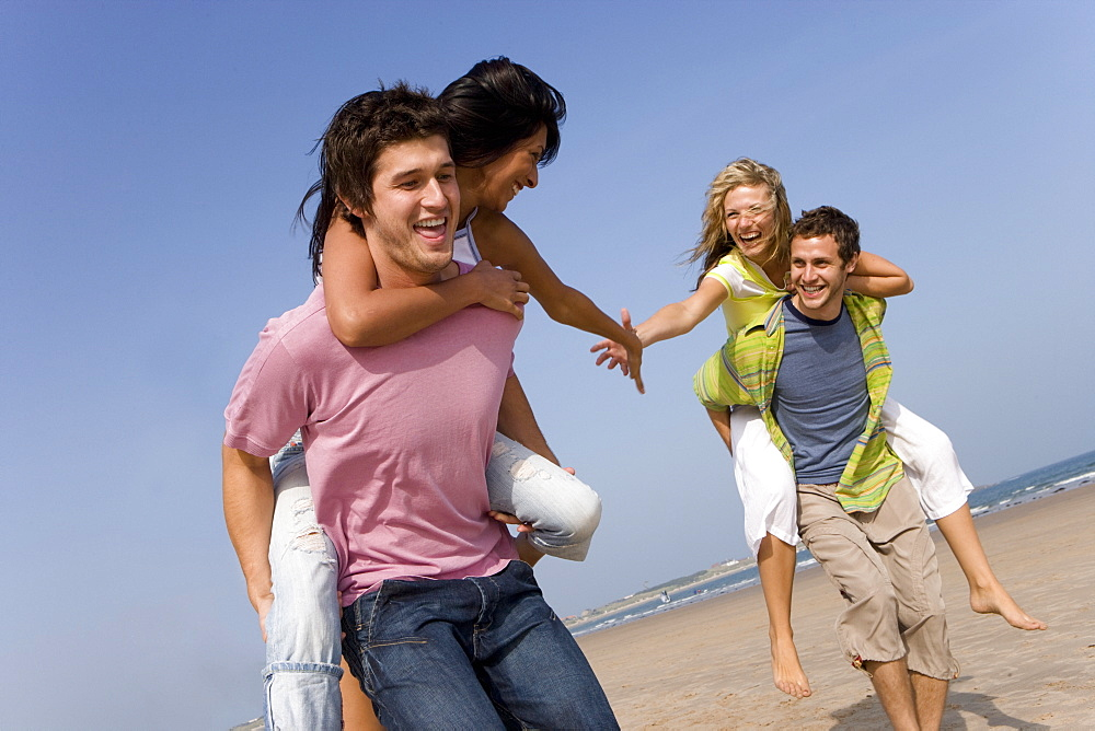 Young men piggybacking women on beach