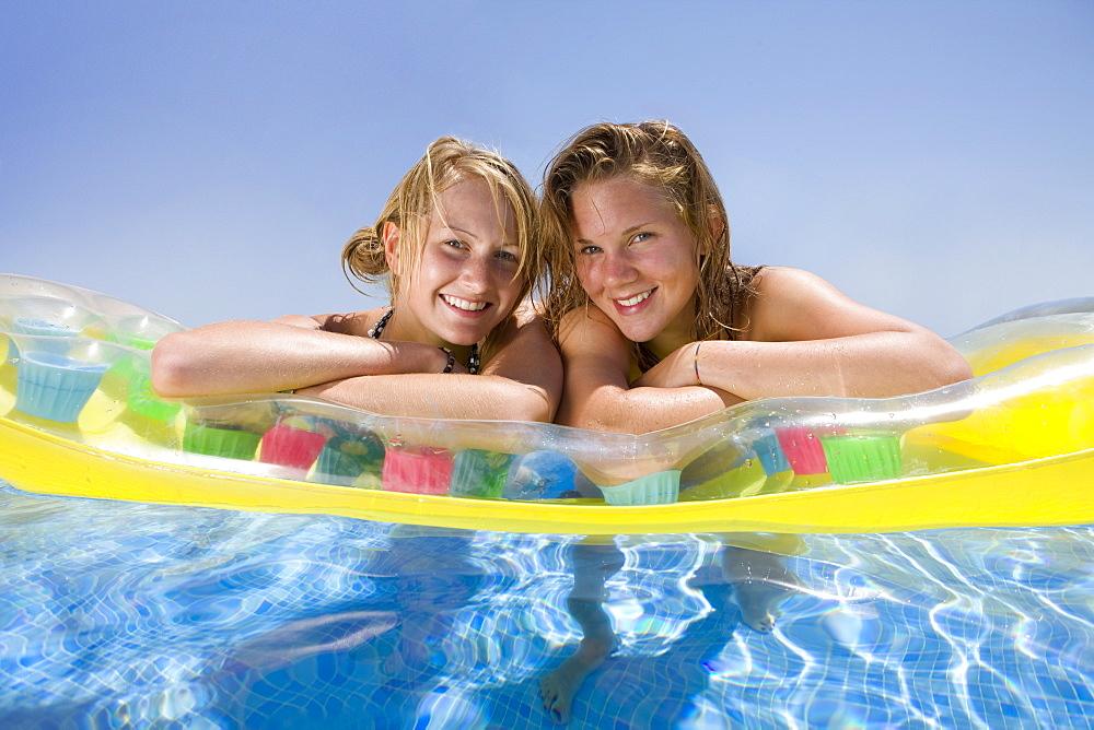 Teenage girls floating in swimming pool - 786-5541
