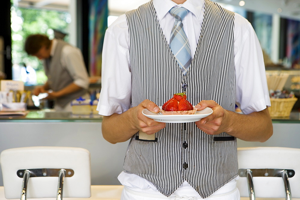 Waiter serving strawberry tart dessert in cafe, front view, mid-section, focus on foreground