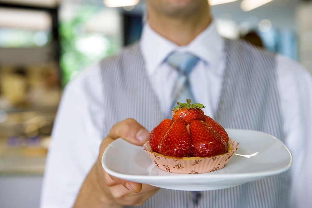Waiter serving strawberry tart dessert in cafe, close-up, front view, focus on foreground