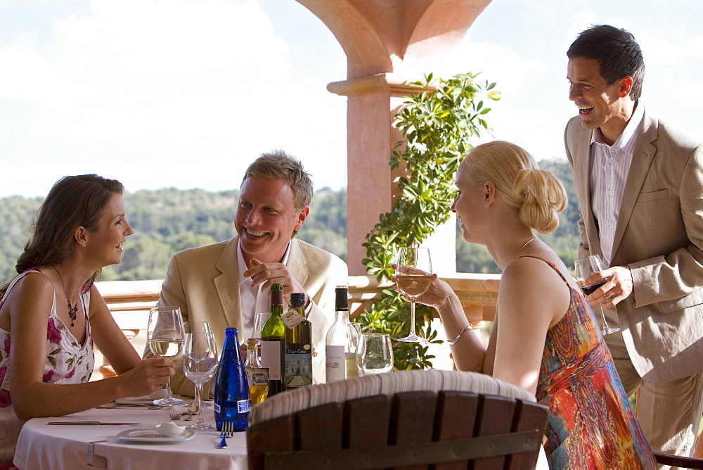 Couples drinking wine at patio table