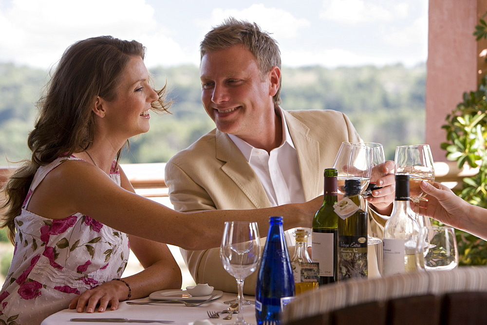 Couples toasting wine glasses at patio table