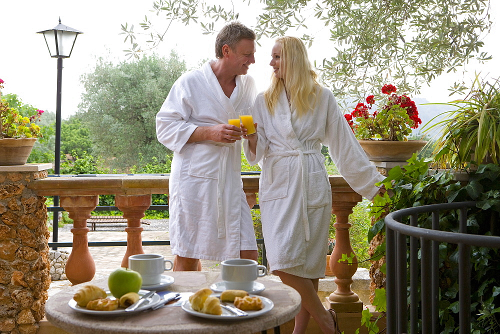 Couple in bathrobes eating breakfast and toasting orange juice glasses on patio