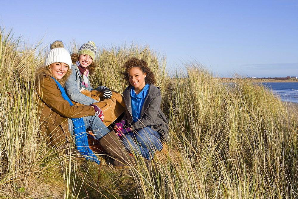 Friends sitting on sand dune near ocean