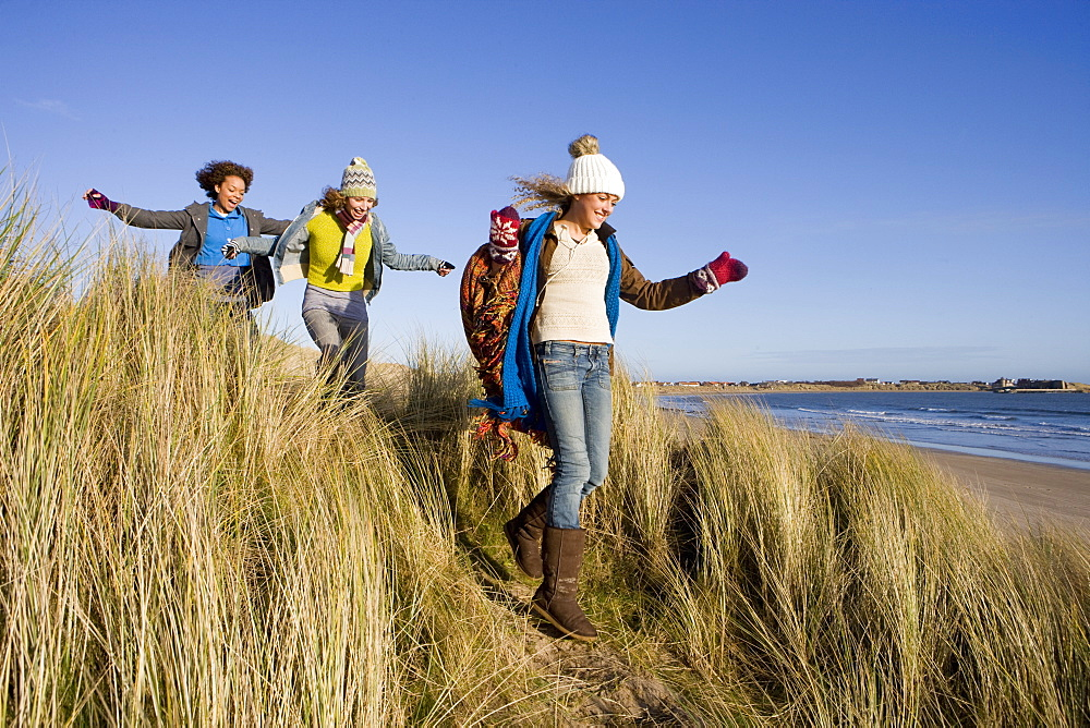 Friends walking on sand dune near beach