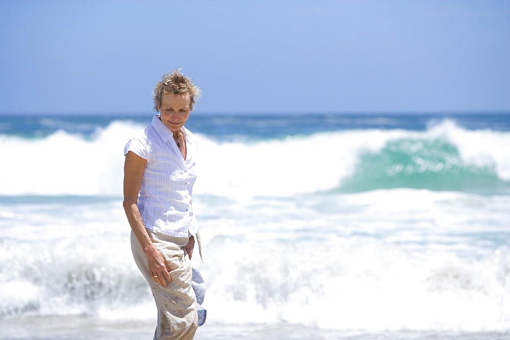 Senior woman standing near ocean at beach