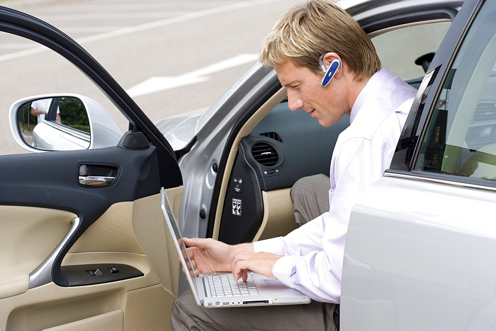 Businessman with bluetooth headset using laptop in car