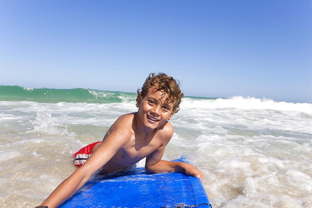 Smiling boy floating on body board in ocean