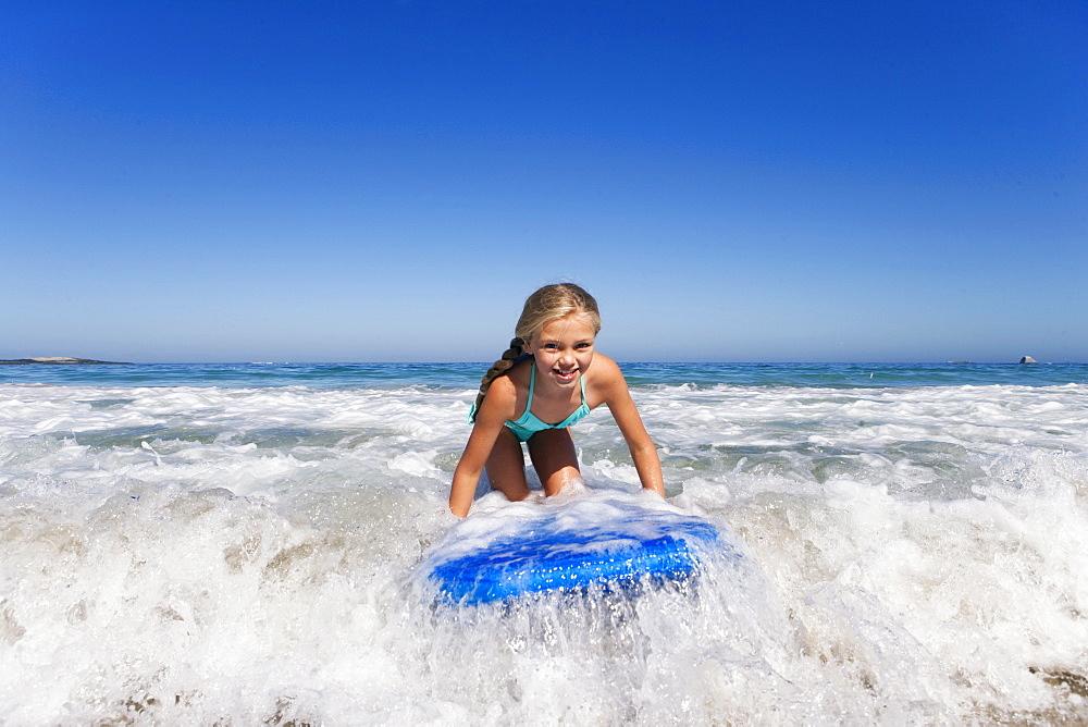 Smiling girl surfing on body board in ocean