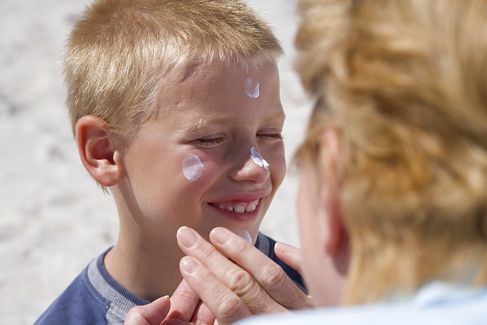 Grandmother applying sunscreen to grandsons face