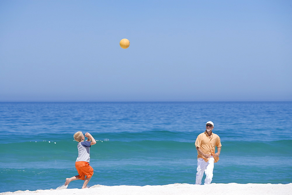 Grandfather playing ball with grandson on beach near ocean