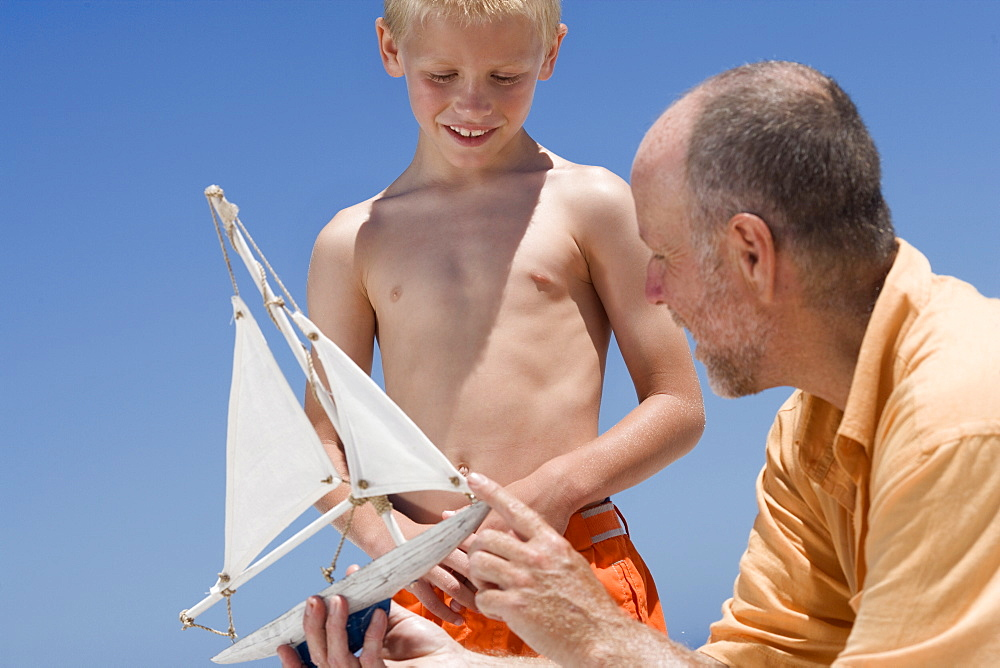 Grandfather showing grandson model sailboat