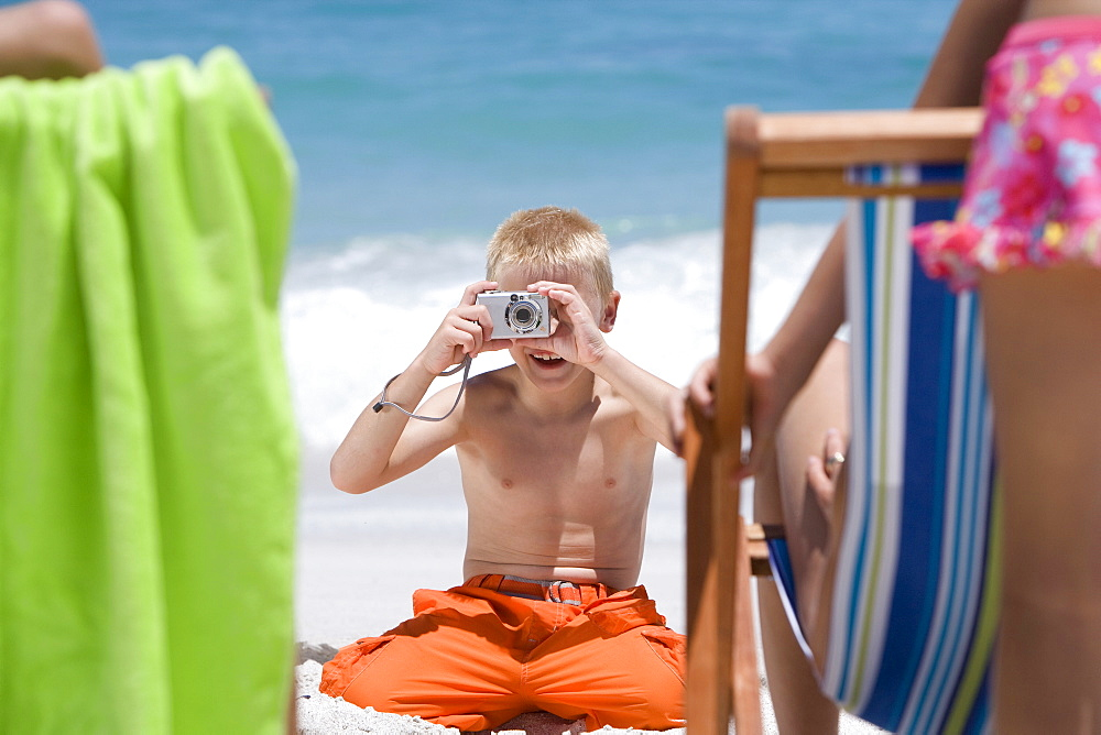 Boy taking photograph at beach of family