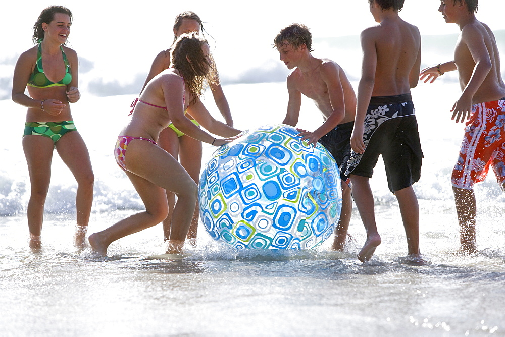Kids wading in ocean and playing with large beach ball