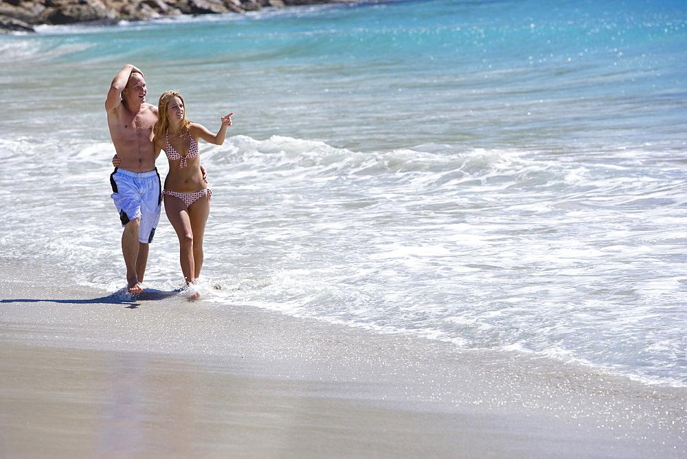 Hugging couple walking through ocean water on beach