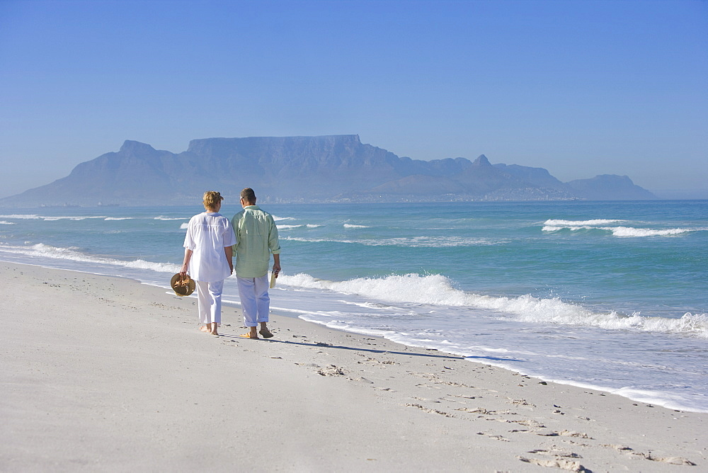 Senior couple walking together on beach near ocean