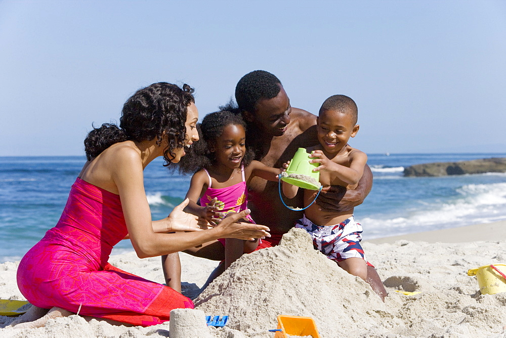 African family making sand castle together on beach