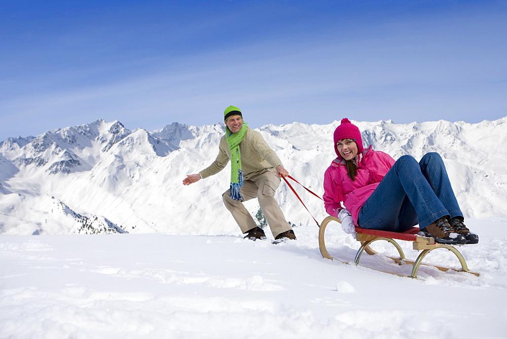 Man pulling woman up ski slope on sled - 786-6502