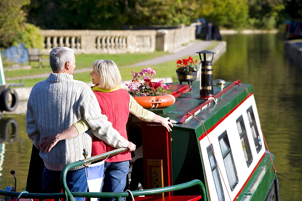 Couple hugging on narrow boat in canal, Somerset, United Kingdom