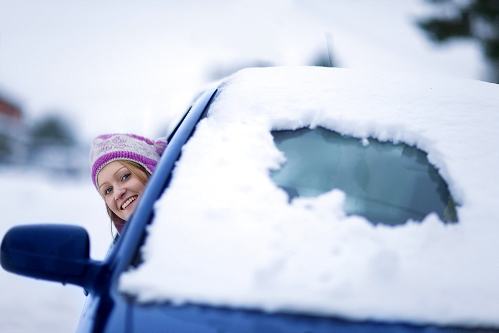 Smiling woman peering out from snow covered car