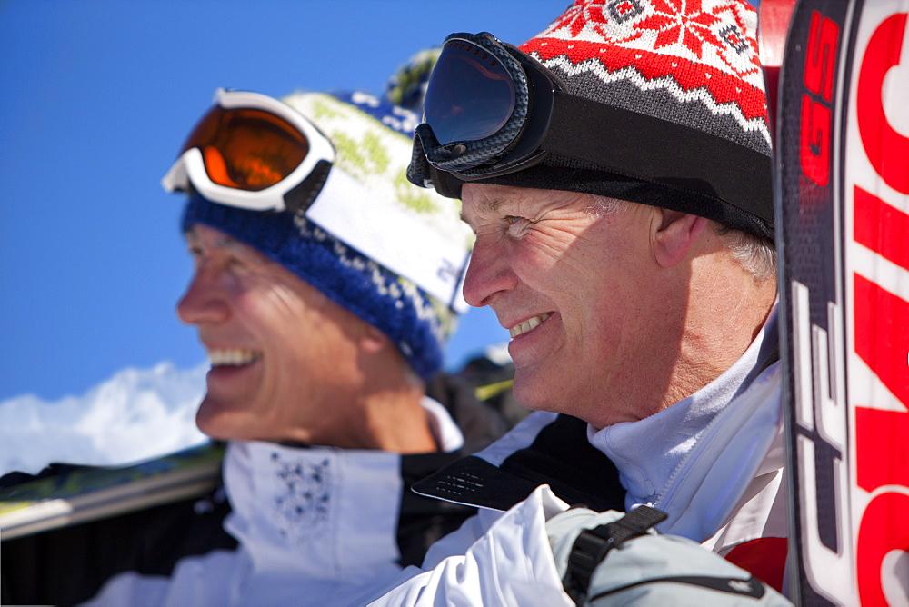 Smiling men standing together holding skis