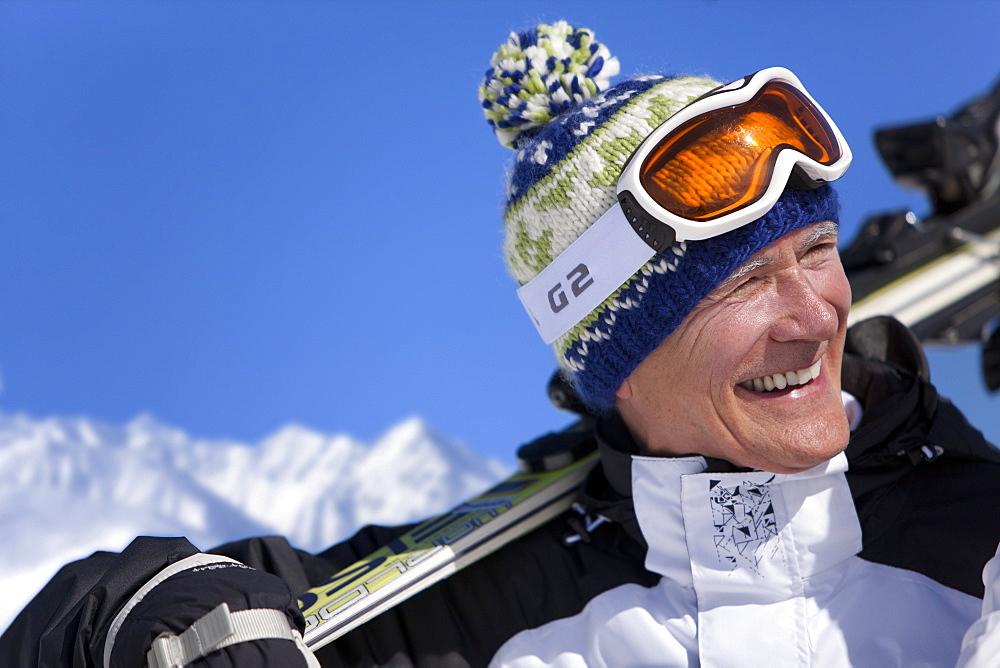 Smiling man standing holding skis
