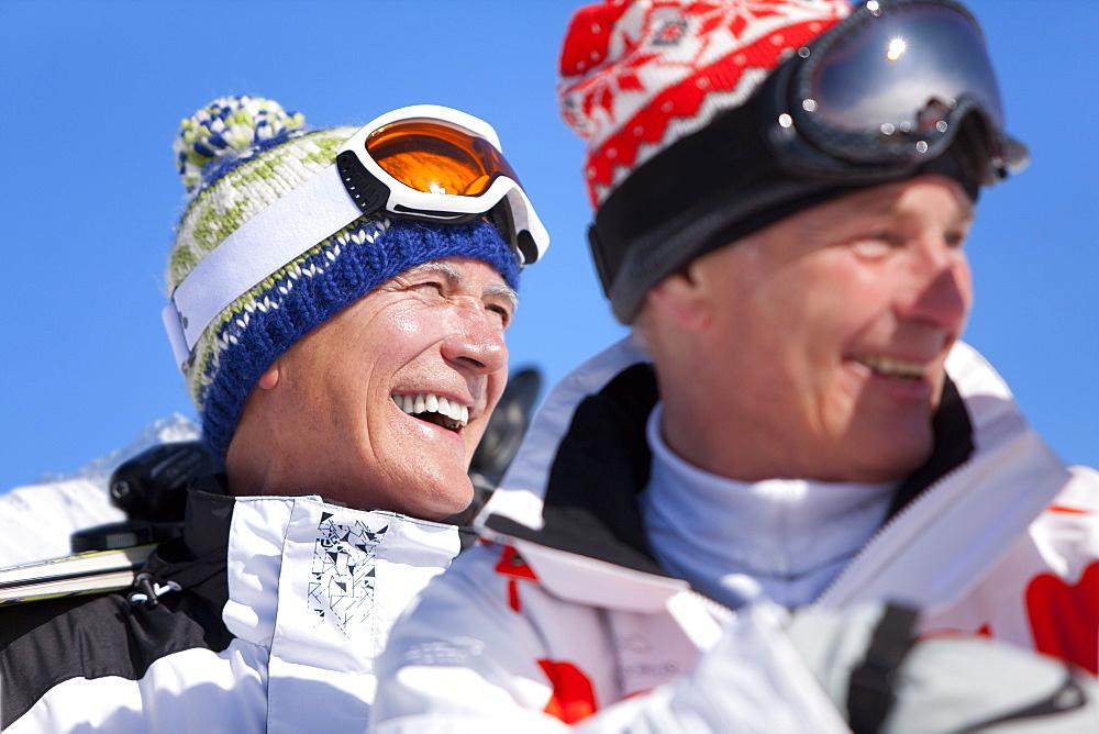 Smiling men standing together in ski goggles