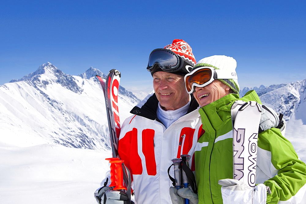 Smiling couple standing together holding skis